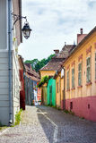 Street lamp on old stone paved street with colored house from Si. Sighisoara, Romania - June 23, 2013: Street lamp on old stone paved street with colored house Stock Image