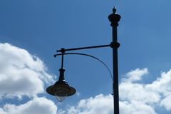 Street lamp pole and light fixture under blue sky. Street lamp pole and light fixture in perspective under blue sky with white clouds stock image