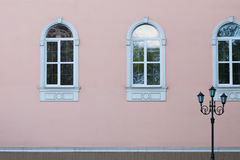 Street lamp post against pink wall. Facade building with retro style windows. Design Stock Photo