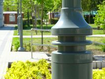 Street lamp post detail in gray color with park-like blurry green background. Street lamp post closeup detail in shiny gray color with park like blurry green stock photos