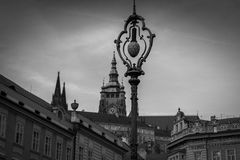 Street lamp in Prague with a watch tower in the background in black and white Royalty Free Stock Photos