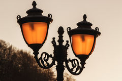 Street lamp in the rays of the setting sun. Street lamp in the Golden rays of the setting sun Stock Photo