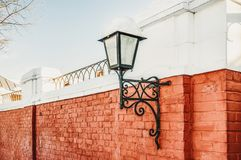 Street lamp on a red brick wall to illuminate the streets of snowy winter.  stock images