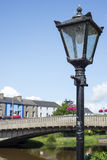 Street lamp and riverside view of town and bridge Stock Photo