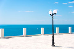 Street lamp on the sea promenade on sunny day Stock Images