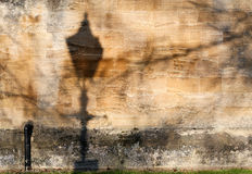 Street lamp shadow on old stone wall texture Royalty Free Stock Photo