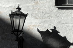 Street lamp with shadow on wall. Retro street lamp with a long shadow on the white painted wall with a window on a sunny day Stock Image