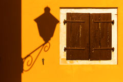 Street lamp shadow on a yellow wall. Street lamp shadow on a yellow wall with wooden shutters Stock Photography