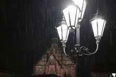 Street lamp shining in the darkness at a rainy night stock image