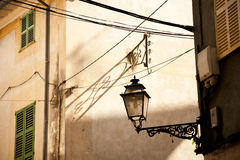 Street Lamp, Valledemosa. Close-up of buildings in Valldemossa, Majorca, Spain with an ornate street lamp and house with green shutters Royalty Free Stock Photos