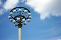 Street lamp with white round shades on a blue sky background royalty free stock photo