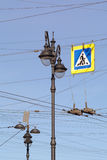 Street lamp, wires, street sign against blue sky Stock Image