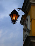 Street lamp on a yellow wall. In the evening Royalty Free Stock Photos