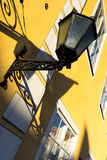 Street lamp on a yellow wall with windows Stock Photo