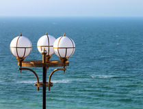 Street lamppost against blue sea background.  Royalty Free Stock Images