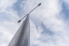 Street lamppost with two searchlights in the daytime against a background of blue sky with white clouds Stock Photos
