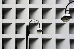Street lamps against Modern abstract urban building. Detailed geometric black and white pattern in city. Street lamps against Modern abstract urban building Royalty Free Stock Images