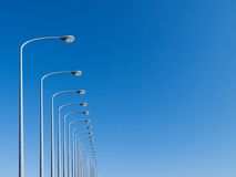 Street lamps aligned. Under big blue sky. Digital composite image stock photos