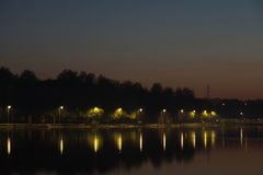 Street lamps on the shore of a pond Stock Image