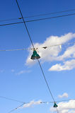 Street lamps on wires against cloudy blue sky Stock Photo