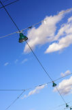 Street lamps on wires against cloudy blue sky Royalty Free Stock Image