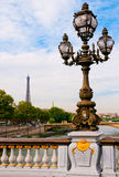 Street lantern on the Alexandre III Bridge. Against the Eiffel Tower in Paris, France Royalty Free Stock Photo