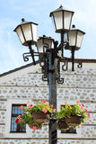 Street Lantern with Flower Pots. In front of a traditional Bulgarian building. Photo shot in the center of Bansko, Bulgaria Stock Image