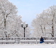 Street lantern with man on the bench cold winter day Royalty Free Stock Images