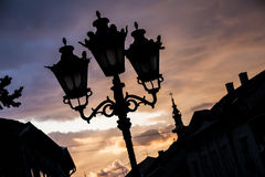 Street lanterns with ortodox church in back. Street lanterns with ortodox church at dawn as silhouettes Stock Image