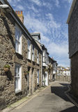 Street leading to harbour at Mousehole. In Cornwall, England UK lined by stone cottages Royalty Free Stock Photo