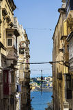 Street leading to the sea on Malta. Typical narrow street leading to the sea on the island of Malta. Buildings with traditional colorful maltese balconies in Stock Photo