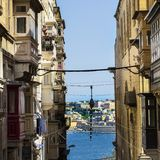 Street leading to the sea on Malta. Typical narrow street leading to the sea on the island of Malta. Buildings with traditional colorful maltese balconies in Stock Photos