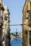 Street leading to the sea on Malta. Typical narrow street leading to the sea on the island of Malta. Buildings with traditional colorful maltese balconies in Stock Photography