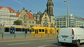 Leipzig public transport and traffic. Street level shot of several tram cars of the Leipzig public transport system meeting in the middle of traffic stock video footage
