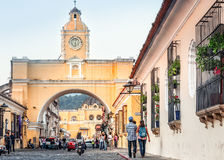 Street life in Antigua. ANTIGUA, Guatemala - March 2, 2016: Santa Catalina Arch and La Merced church in the distance in Antigua, old historic city in Guatemala Stock Images