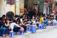 Street life in Hanoi, Vietnam. Typical street life in Hanoi. Locals gather on plastic chairs to have a drink or some food Stock Photos