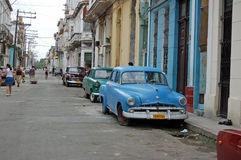 Street life, Havana. HAVANA, CUBA - NOVEMBER 19, 2005: Pedestrians and parked classic cars in a residential street in Havana's Vedado district.  Fuel is in short Royalty Free Stock Photography