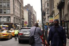 Street life in New York. New York, United States - 31 August 2016. People walking in the street, a man lost in thought on the right Stock Image