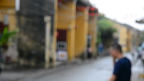 Street life in out of focus. People and vehicles on the street in Hoi An, Vietnam. The photo is purposely made out of focus, no faces are recognisible stock video