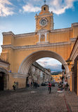 Street life under Santa Catalina Arch in Antigua. Antigua, Guatemala -March 3, 2016: Santa Catalina Arch against the blue sky close to sunset in Antigua Stock Photos