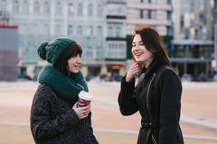 Street Lifestyle portrait of two beautiful, smiling and very stylish girls who communicate with each other. Street Lifestyle portrait of two beautiful, smiling Royalty Free Stock Photos