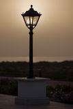 Street light. Sun setting behind an antique street light Royalty Free Stock Photo
