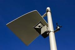 Street light. Perspective view of a modern design street light against a deep blue sky.Wind meter on it stock photos