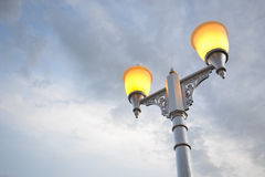 Street light. At dusk on gray sky background Royalty Free Stock Photos