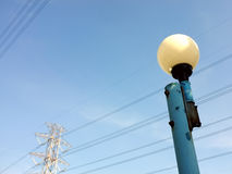 close-up blue street light pole with white round lamp and high voltage tower under blue sky Stock Images