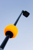 Street light pole with lighted globe and blue sky. Photo of street light pole with lighted globe and blue sky Stock Photo