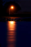 Street Light Reflecting on Water. A street light reflecting over the ocean at night Stock Photography