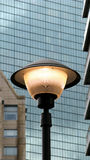 Street light and skyscraper. Closeup of lighted street lamp with glass windows of modern skyscraper building in background Royalty Free Stock Photos