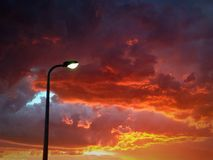 Street light sunset. A streetlight comes on just as the sun goes down royalty free stock photos