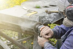 Free Street Lighting. A Masked Worker Processes A Granite Stone With A Special Tool. Close-up Stock Photo - 219219780